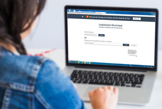 Audiodescrição: A imagem tem o fundo levemente desfocado, e mostra uma mulher usando um notebook. Ela está acessando a nova plataforma de Legislação Municipal do TCE-RS (fim da descrição).